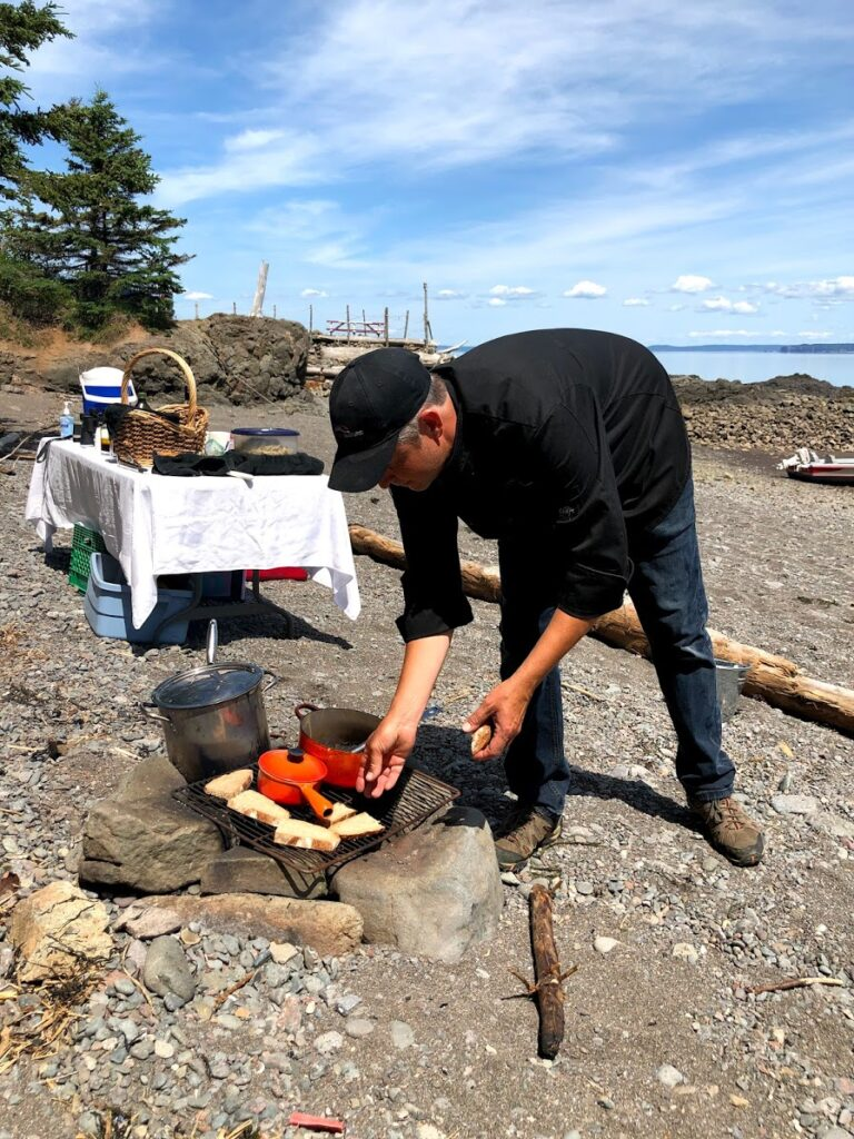 Wild Chef Sean Laceby toasting sourdough bread and cooking wild periwinkles and seaweed.