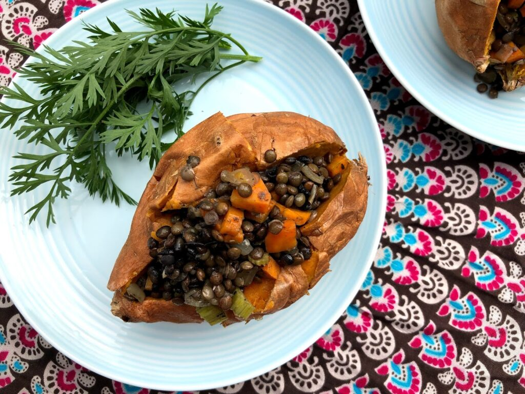Lentil Stuffed Sweet Potato with carrot top garnish.
